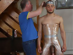 Nathaniel has been away for so long, Sebastian decided it was time for one last adventure before sending Nathaniel on his way. Weak and submissive, Nathaniel is willing to do anything if it means his freedom. Sebastian decides to string the lad up, work his drained cock, before restraining the lad with cling-film to a hand post. Unable to move a muscle, Nathaniel begs Sebastian not to tease his tired dick. It's no secret how much Seb loves taking cum from hot lads and this time was to be no exception. Watch as Nathaniel, held up only by the cling-film, gets bought to climax, legs shacking as his load releases and falls to the floor. Head hung, drained and humiliated, Nathaniel is told its time for him to go.